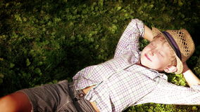 Sun pierces through the tree leaves and wakes up the boy sleeping on the grass stock footage