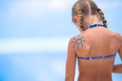 Sun pintou pelo creme do sol no ombro da criança fotografia de stock royalty free