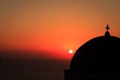 Sun plaçant au-dessus d'une église dans le village d'Oia, Santorini Photographie stock libre de droits