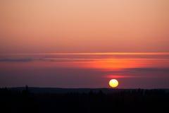 Sun plaçant au-dessus de la forêt Photographie stock libre de droits
