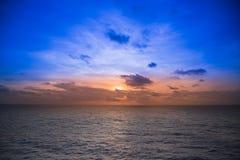 Sun a placé avec le ciel bleu en mer Photo stock