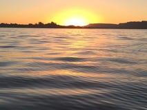 Sun a placé sur l'eau Photographie stock libre de droits