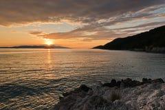 Sun place derrière l'île de Skiathos avec quelques roches de mer dans le premier plan à la plage de Mia de maman de Kastani, île  photo stock