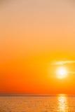 Sun place sur l'horizon au lever de soleil de coucher du soleil au-dessus de la mer ou de l'océan Images libres de droits