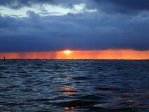 Sun plonge au-dessous des nuages pendant qu'il s'abaisse à l'océan images stock