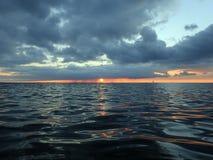 Sun plonge au-dessous des nuages pendant qu'il s'abaisse à l'océan pacifique photographie stock libre de droits
