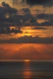 Sun plongeant lentement dans l'océan, couvert par les nuages minces et indécis Photo stock