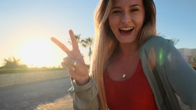 Sun portrait of attractive girl in red swimsuit looking at camera and making peace sign with hand or V sign with fingers stock footage