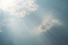 Sun projecting rays behind dramatic clouds in the blue sky before a thunderstorm stock photo