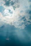 Sun projecting rays behind dramatic clouds in the blue sky before a thunderstorm royalty free stock photography