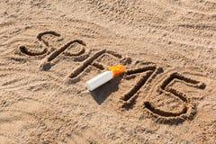 Sun prot?gent le facteur quinze Mot de la SPF 15 ?crit sur le sable et la bouteille blanche avec de la cr?me de bronzage Fond de  photo libre de droits