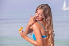 Sun protecion woman with suntan lotion Stock Images
