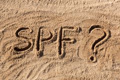 Sun protect factor concept. SPF word written on the beach with question mark.  royalty free stock photography