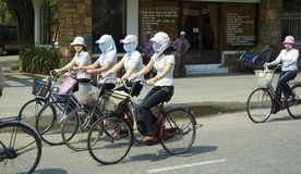 Sun protection. Five girls on bicycles in Hue,Viet Nam dressed for sun protection Royalty Free Stock Image