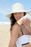 Sun protection. Beautiful woman at the beach putting sunscreen on her body Royalty Free Stock Photography