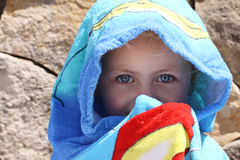 Sun protection. A little girl totally covered with a towel after swimming to protect against the damage of the sun Royalty Free Stock Photo