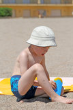 Sun protection. 5 years old kid applying suntan lotion on the beach stock photography