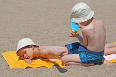 Sun protection. Two brothers applying suntan lotion on the beach stock photography