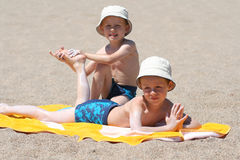 Sun protection. Two brothers applying suntan lotion on the beach stock photos