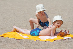 Sun protection. Two brothers applying suntan lotion on the beach royalty free stock images