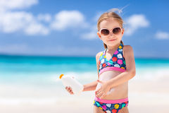 Sun protection. Adorable little girl at tropical beach applying sunblock cream Stock Photos