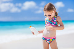 Sun protection. Adorable little girl at tropical beach applying sunblock cream Royalty Free Stock Photo