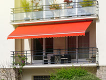 Sun protection awning at French balcony. French balcony with awning opened covered by sun-shield on a warm summer day royalty free stock photos