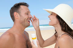 Sun protection at the beach. Woman putting sunblock on her boyfriend's nose Stock Image