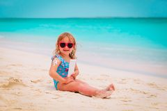 Sun protection on beach- little girl applying sunblock cream on shoulder. Sun protection at beach- little girl applying sunblock cream on shoulder at sea Royalty Free Stock Images