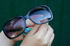 Sun-protection brown glasses in the hands of a girl Stock Images