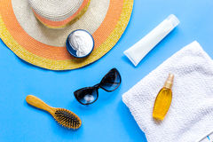 Sun protection composition with glasses and cream on blue background top view Stock Image
