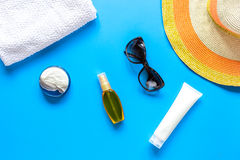 Sun protection composition with glasses and cream on blue background top view Royalty Free Stock Images