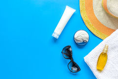 Sun protection composition with glasses and cream on blue background top view mockup Stock Image