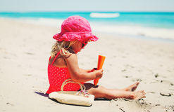 Sun protection concept - little girl with suncream at beach Royalty Free Stock Image