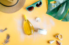 Sun protection cosmetic cream with beach outfit on orange background top view Stock Images