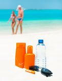 Sun protection cream, water and sun glasses Royalty Free Stock Photos