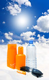 Sun protection cream, water and sunglasses Stock Image