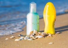 Sun protection creams on a seashore, sandy beach Stock Images
