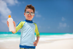 Sun protection. Cute little boy at tropical beach holding a bottle of sunblock Stock Images