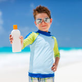 Sun protection. Cute little boy at tropical beach holding a bottle of sunblock Stock Image
