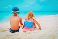 Sun protection- little boy and girl with suncream at beach royalty free stock image