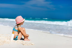 Sun protection. Little girl with bottle of sun cream sitting at tropical beach Royalty Free Stock Photos