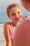 Sun protection-mother anoints her daughter face protective cream Royalty Free Stock Photography