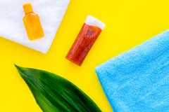 Sun protection products. Bottles with cream or lotion near towel and palm leaves on yellow background top view copy stock image