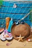 Sun protection still life on the beach. Sun protection still life with suntan lotion bottles, straw hat,sunglasses,flip-flops and shells on the beach Royalty Free Stock Photos