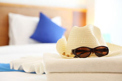 Sun Protection in Summer. Sun glasses and hat on the bed in hotel Royalty Free Stock Photography