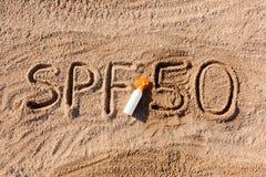 Sun protege el factor cincuenta Palabra del SPF 50 escrita en la arena y la botella blanca con crema del bronceado Fondo del conc fotos de archivo