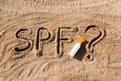 Sun protege factor Palabra del SPF escrita en la arena y la botella blanca con crema del bronceado con el signo de interrogaci?n  fotos de archivo libres de regalías