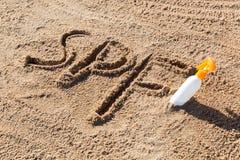Sun protege factor Palabra del SPF escrita en la arena y la botella blanca con crema del bronceado Fondo del concepto del cuidado foto de archivo libre de regalías