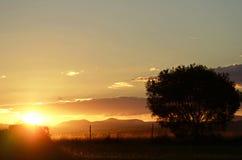 Sun que ajusta-se sobre montanhas como o dia termina a cidade de país rural fotos de stock